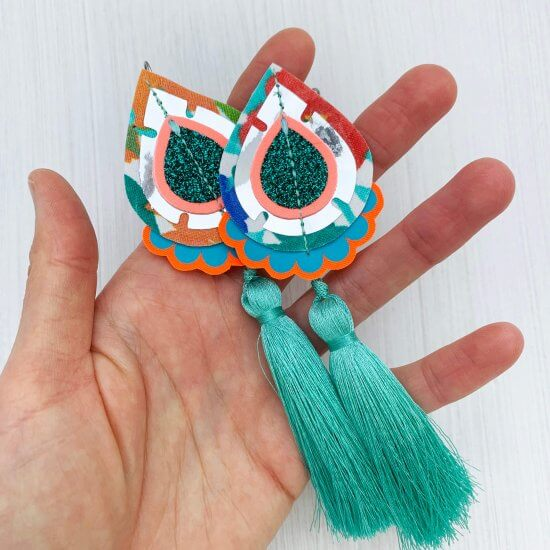 A pair of teardrop shaped, dakota rae dust Statement tassel earrings cut from vintage floral fabric, adorned with turquoise green silky tassels are held in a woman's hand against an off white background.