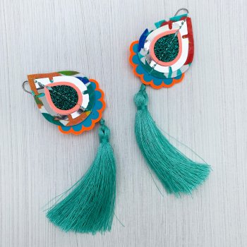 A pair of teardrop shaped Tassel earrings cut from vintage floral fabric, with turquoise green silky tassels seen lying on a plain off white background.