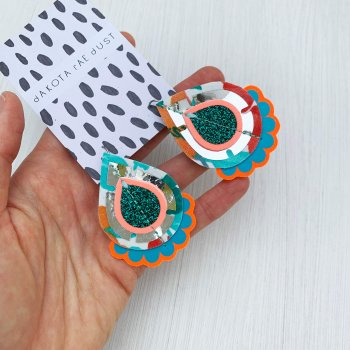 A pair of decorative teardrop shaped, vintage fabric earrings are held in a woman's hand against a white background. The large teardrop shape component is cut from a vintage floral fabric.
