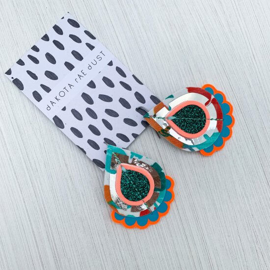 teardrop shaped colourful statement earrings displayed on a black and white patterned backing card against a white background.