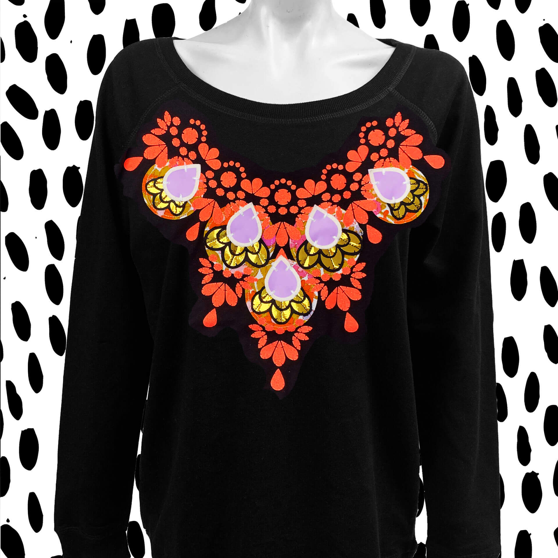 A black wide neck sweatshirt worn by a white mannequin, against a black and white patterned background. The sweatshirt has a decorative neon coral, gold and lilac print over the bib area.