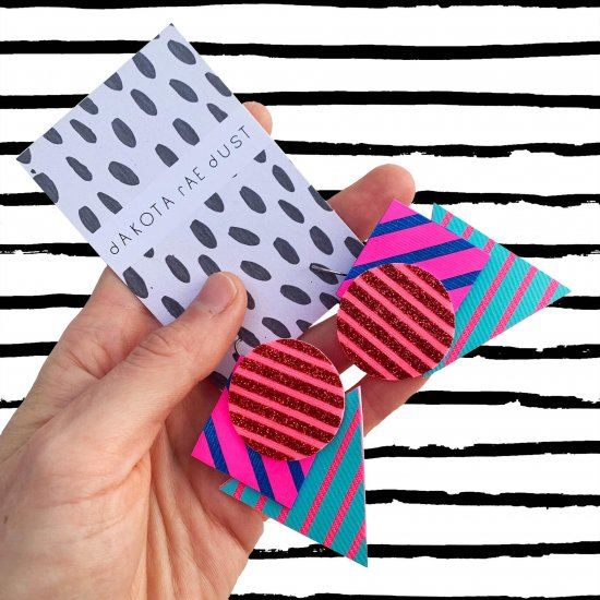 A pair of colourful dakota rae dust Triangular stripe earrings, featuring a cluster of three geometric shapes printed with bold graphic stripes displayed on a black and white patterned, dakota rae dust branded card, held in a white woman's hand with a black and white striped background