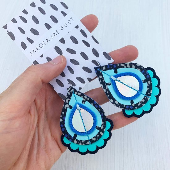 A pair of decorative teardrop earrings in shades of blue and silver mounted on a black and white patterned dakota rae dust branded card, held in a woman's hand against an off white background