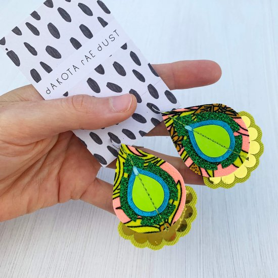 A pair of green, lime, peach and gold patterned fabric earrings, mounted on a black and white patterned dakota rae dust branded card, against an off white background