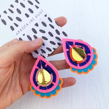 A pair of glittery teardrop earrings in pink, blue and gold, mounted on a black and white patterned dakota rae dust branded card are held in a woman's hand against an off white background