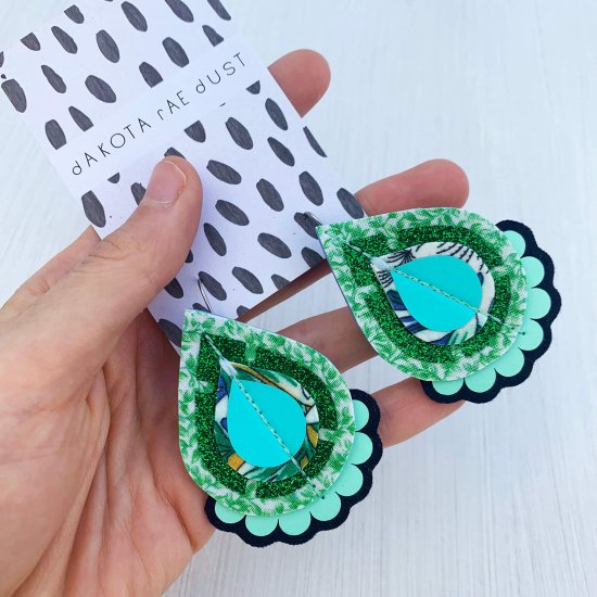 A pair of glittery green teardrop earrings cut from vintage green and white patterned fabric mounted on a black and white patterned dakota rae dust branded card, held in a woman's hand, photographed against an off white background