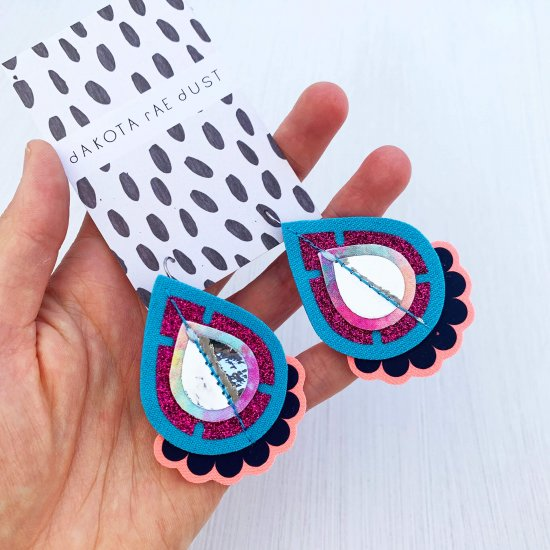 A pair of turquoise and pink colourful statement earrings, mounted on a black and white patterned dakota rae dust branded card are held in a woman's hand against an off white background