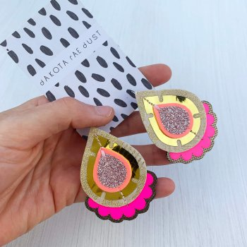 A pair of shiny gold and fluorescent pink teardrop shaped earrings, backed on a black and white patterned branded card are held in a woman's hand against an off white background