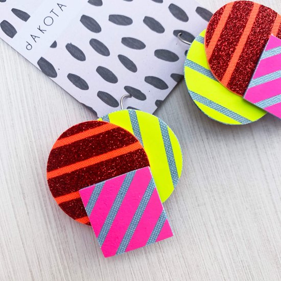A pair of colourful Stripey shapes earrings, featuring a cluster of three geometric shapes printed with bold graphic stripes are seen displayed on a black and white patterned, dakota rae dust branded card, against an off white background.