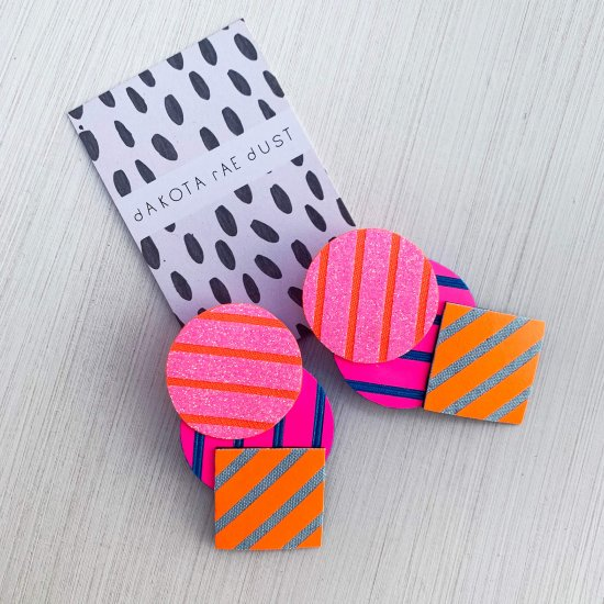 A pair of colourful graphic stripe earrings, made from three stripey geometric shapes, two circles and a square are seen displayed on a black and white patterned, dakota rae dust branded card, against an off white background.