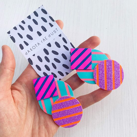A pair of colourful stripey cluster earrings, featuring boldly striped geometric shapes in pink, blue, turquoise and purple glitter, displayed on a black and white patterned, dakota rae dust branded card, held in a woman's hand.