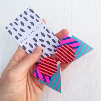 A pair of colourful Triangular stripe earrings, featuring a cluster of three geometric shapes printed with bold graphic stripes displayed on a black and white patterned, dakota rae dust branded card, held in a white woman's hand with an off white background