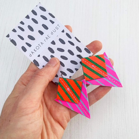 A pair of fluorescent pink, red andemerald green Stripey triangle earrings, featuring a triangle and square printed with bold graphic stripes displayed on a black and white patterned, dakota rae dust branded card, held in a white woman's handagainst an off white background