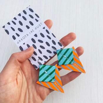 A pair of fluorescent orange, green and blue Stripey triangle earrings, featuring a triangle and square printed with bold graphic stripes displayed on a black and white patterned, dakota rae dust branded card, held in a white woman's hand against an off white background