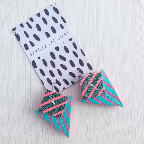 A pair of turquoise, fluorescent pink and emerald green glitter Stripey triangle earrings, featuring a triangle and square printed with bold graphic stripes displayed on a black and white patterned, dakota rae dust branded card, against an off white background