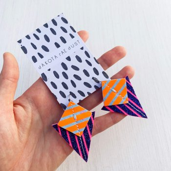 A pair of glittery blue, pink, orange and pale blueStripey triangle earrings, featuring a triangle and square printed with bold graphic stripes displayed on a black and white patterned, dakota rae dust branded card, held in a white woman's handagainst an off white background