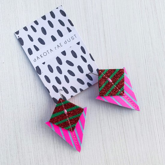 A pair of fluorescent pink, glittery red, green and pale blueStripey triangle earrings, featuring a triangle and square printed with bold graphic stripes displayed on a black and white patterned, dakota rae dust branded card, against an off white background