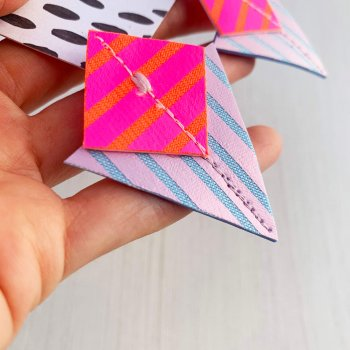 A pair of lilac, fluorescent pink, orange and pale blue Stripey triangle earrings, featuring a triangle and square printed with bold graphic stripes displayed on a black and white patterned, dakota rae dust branded card, held in a white woman's hand against an off white background