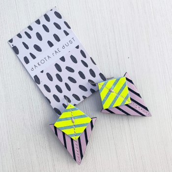A pair of lilac, fluorescent yellow and navyStripey triangle earrings, featuring a triangle and square printed with bold graphic stripes displayed on a black and white patterned, dakota rae dust branded card, against an off white background
