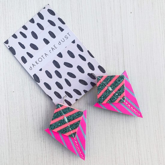 A pair of fluorescent pink, emerald glitter and pale blueStripey triangle earrings, featuring a triangle and square printed with bold graphic stripes displayed on a black and white patterned, dakota rae dust branded card against an off white background