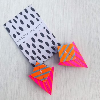 A pair of fluorescent pink, orange and blue Stripey triangle earrings, featuring a triangle and square printed with bold graphic stripes displayed on a black and white patterned, dakota rae dust branded card, against an off white background