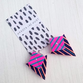 A pair of glittery blue and pink Stripey triangle earrings, featuring a triangle and square printed with bold graphic stripes displayed on a black and white patterned, dakota rae dust branded card, against an off white background