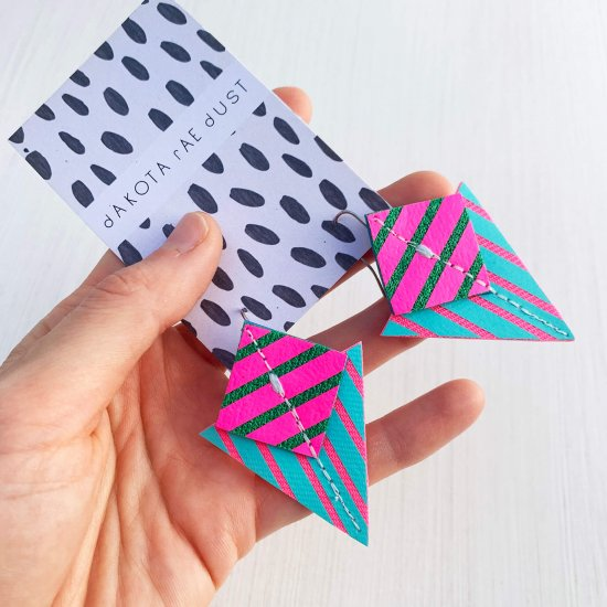 A pair of turquoise, fluorescent pink and greenStripey triangle earrings, featuring a triangle and square printed with bold graphic stripes displayed on a black and white patterned, dakota rae dust branded card, held in a white woman's handagainst an off white background