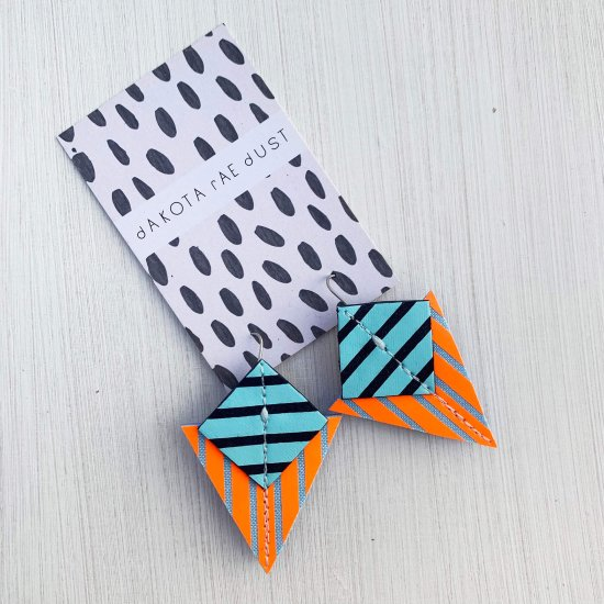 A pair of fluorescent orange, navy and pale blue Stripey triangle earrings, featuring a triangle and square printed with bold graphic stripes displayed on a black and white patterned, dakota rae dust branded card against an off white background