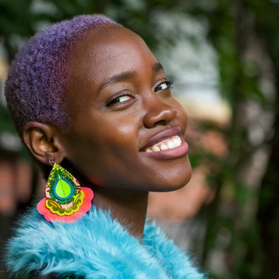A young black woman with cropped lilac hair wears a pair of colourful, oversize statement earrings and a bright blue faux fur wrap. She is smiling and looking sideways, over her shoulder, into the camera.