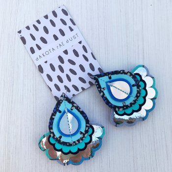A pair of teardrop shaped, statement oversize earrings in multiple shades of blue and silver are seen mounted on a black and white patterned dakota rae dust branded card, against an off white background