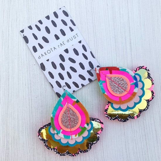 A pair of decorative teardrop shaped, recycled fabric earrings with a gold scallop edged frill and fluorescent pink / glittery silver middle mounted on a black and white patterned dakota rae dust branded card against an off white background