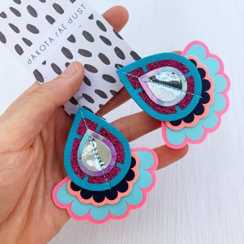 A colourful pair of teardrop shaped oversize earrings in turquoise and pink and held in a white woman's hand against an off white background