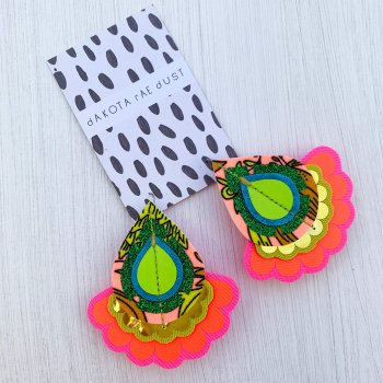 A pair of decorative teardrop shaped, colourful festival earrings in glittery green, red, peach, lime and gold mounted on a black and white patterned dakota rae dust branded card, photographed against an off white background