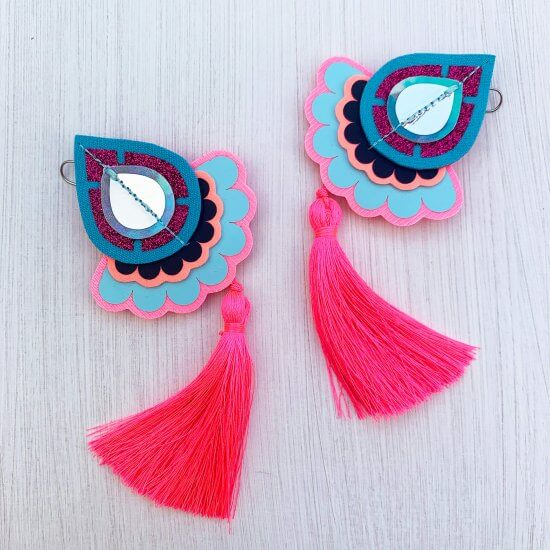 A pair of decorative teardrop shaped statement tassel earrings in pink and turquoise against an off white background