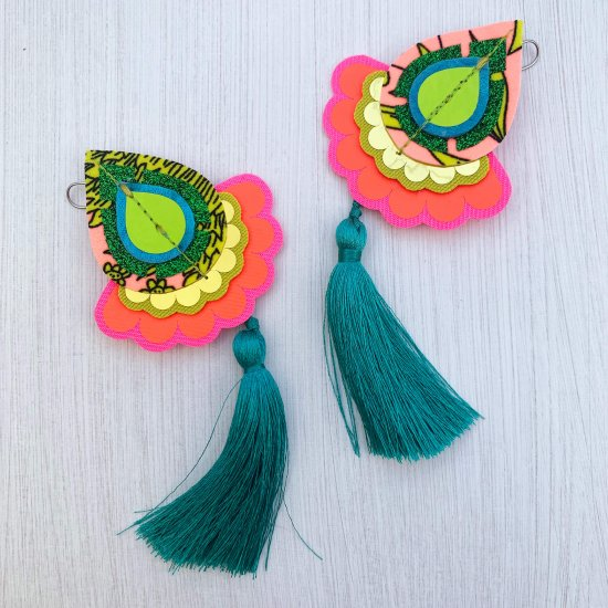 A pair of decorative teardrop shaped, statement tassel earrings in emerald green, red, lime and peach mounted on a black and white patterned dakota rae dust branded card, held in a woman's hand against an off white background