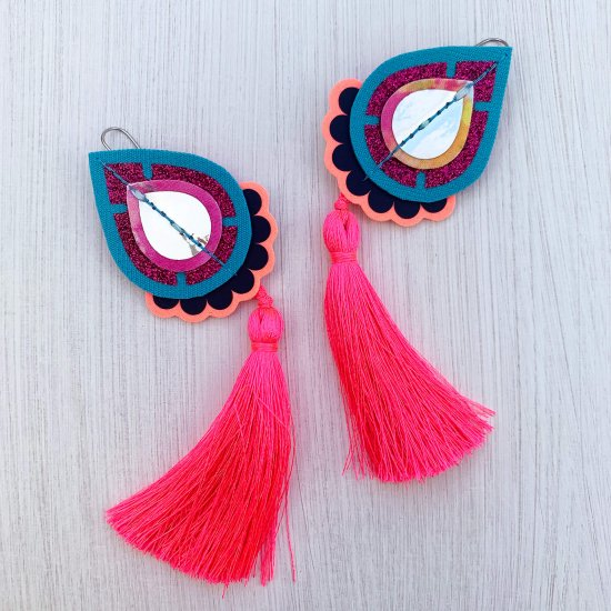 A pair of decorative teardrop shaped, neon pink tassel earrings mounted on a black and white patterned dakota rae dust branded card, photographed against an off white background