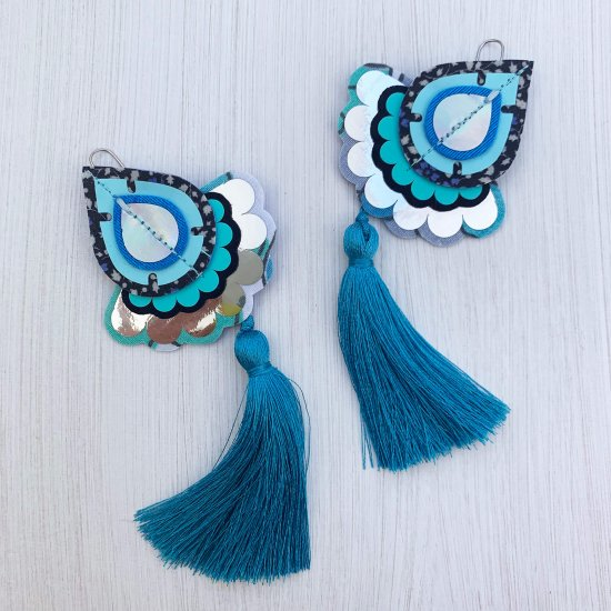 A pair of decorative teardrop shaped statement tassel earrings in shades of blue and silver mounted on a black and white patterned dakota rae dust branded card, photographed against an off white background