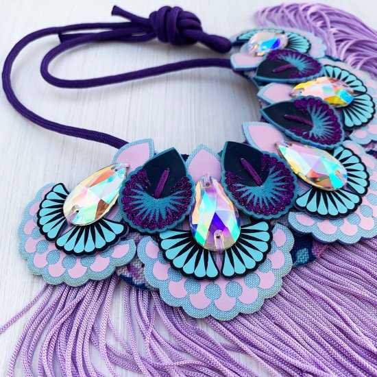 A lilac, light blue and purple statement jewel bib necklace with a lilac fringe photographed against an off white background