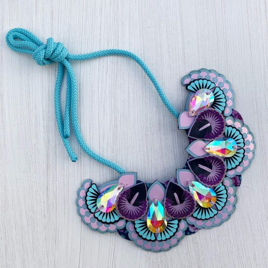 A lilac, light blue and purple statement jewel bib necklace photographed against an off white background