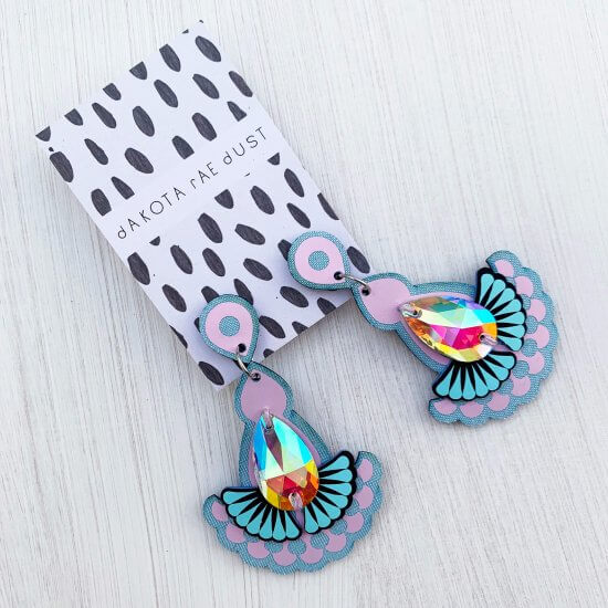 A pair of pale blue and lilac, fan shaped Statement jewel earrings adorned with an iridescent gem are seen mounted on a black and white patterned, dakota rae dust branded card against an off white background
