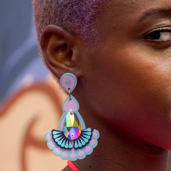 close up of a young black woman with short lilac hair wearing an ornate teardrop shaped statement jewel earring. The side of her face and ear are in focus, the grey blue and peach block colour background os blurred.