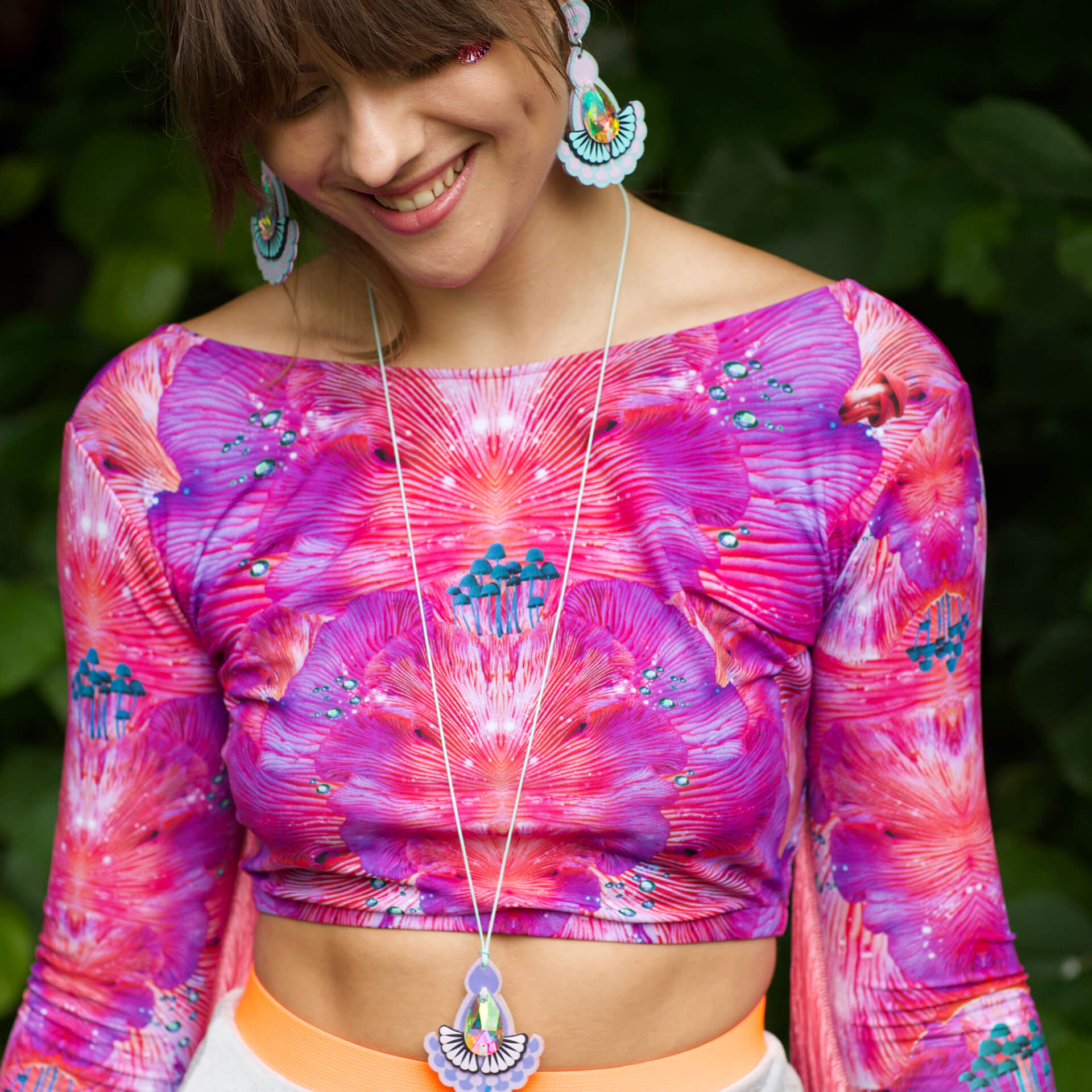 A young woman wearing a bright pink patterned, long sleeved lycra crop, lilac statement earrings and a pendant necklace with a long cord is looking down at the ground and smiling.