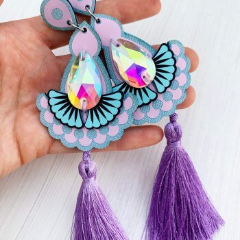 A pair of lavender, lilac and light blue statement jewel earrings, featuring silky tassels and iridescent gems held in a white woman's hand against an off white background