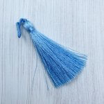 A silky mid blue tassel lying on an off white background