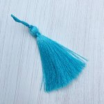 A silky light turquoise tassel lying on an off white background