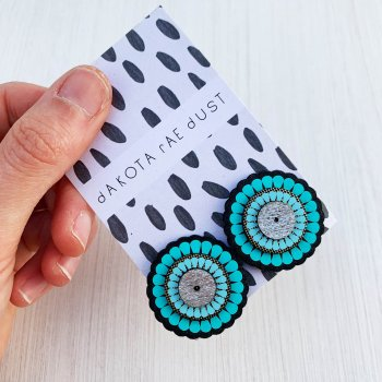 A pair of laser cut ornate and oversize turquoise stud earrings mounted on a black and white patterned dakota rae dust branded card held in a white woman's hand against an off white background