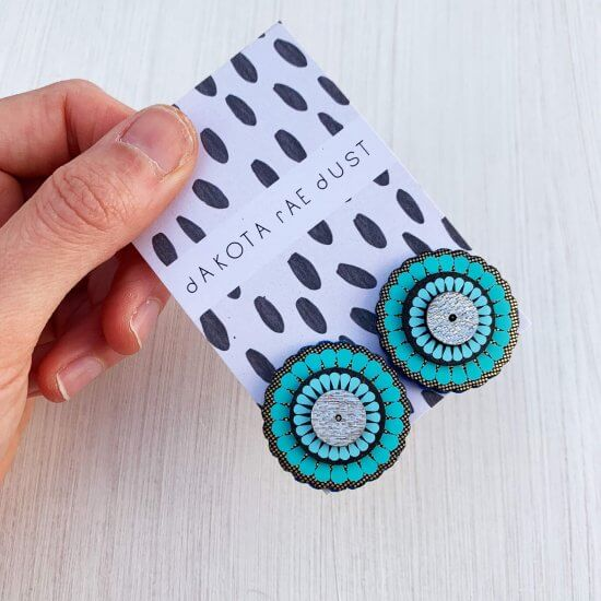 A pair of oversize turquoise gold studs mounted on a black and white patterned, dakota rae dust branded card held in a white woman's hand against an off white background