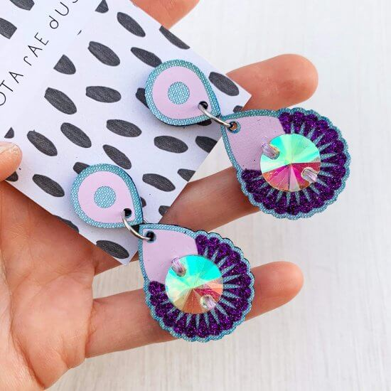 A pair of lilac and light blue dangly jewel earrings mounted on a black and white patterned, branded dakota rae dust card and held in a white woman's hand