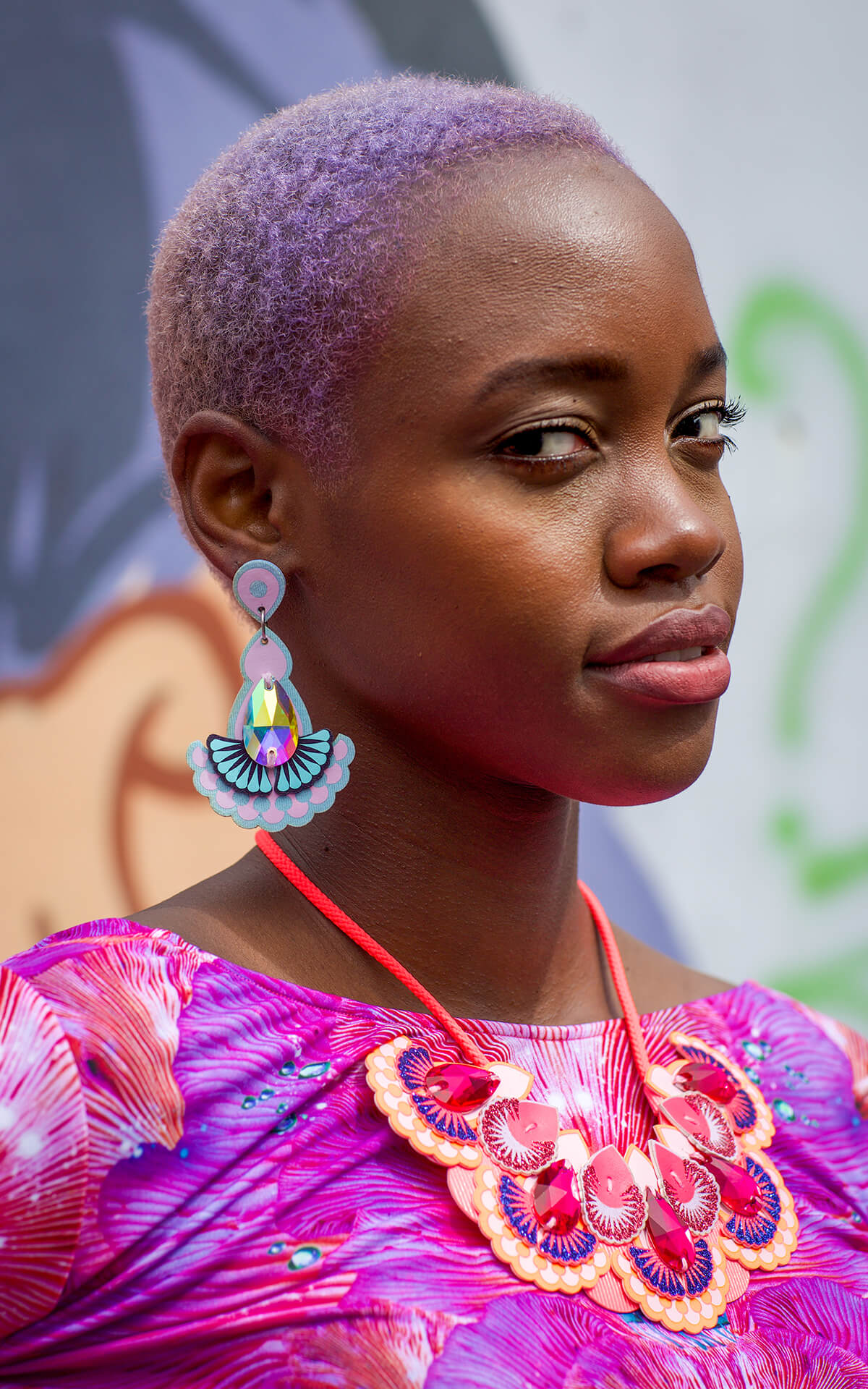 A portrait photo of Cidella, a young black woman with short lilac hair wearing a bright pink top and a colourful pair of laser cut fabric earrings and bib necklace