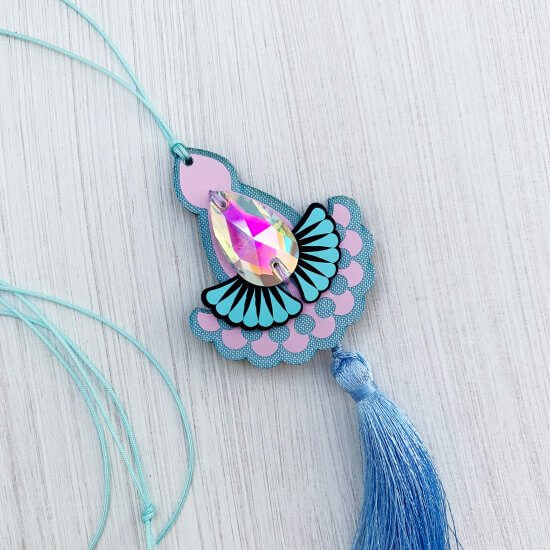 A lilac and light blue, laser cut jewel pendant necklace with an iridescent jewel and light blue thin cord are seen against a textured white background